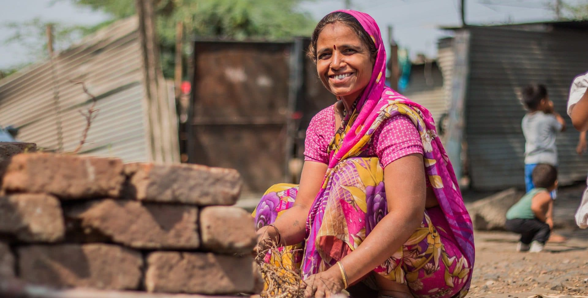 Speridian-Technologies E-village snap ofLady crouching and smiling in village